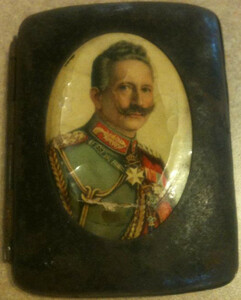 A small rusted metal cigarette case with a portrait of Kaiser Wilhelm II.