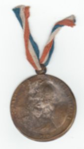 A photograph of a tarnished medal with a ribbon