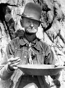 Black and white photo of the same man, holding a gold pan