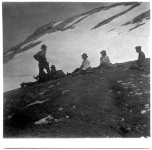 Black-and-white photo of several people resting on a mountain side.