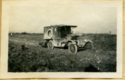 Black and white photograph of a Model T Ford ambulance on a muddy road