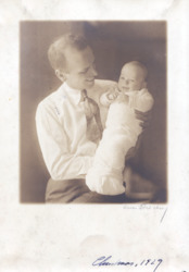 Photograph of a smiling man holding a baby in swaddling clothes.